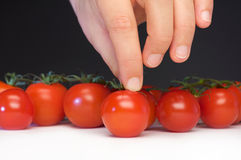 Take a tomato. Women catch a tomato from the table Royalty Free Stock Photography