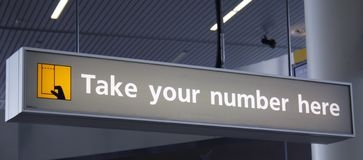 Take your number here. Grey sign with yellow pictogram and text take your number here Stock Photos