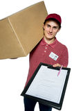 Take your package! Happy young courier man holding a paper box Stock Photo