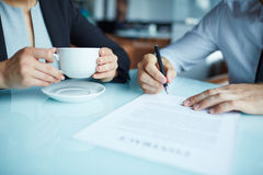 Take your signiture. Businessman signing a contract at cafe Royalty Free Stock Image