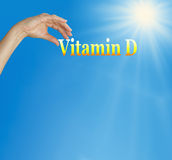 Take your Vitamin D. Sunshine and blue sky background with the word Vitamin D and a female hand positioned under the D with plenty of copy space below royalty free stock images