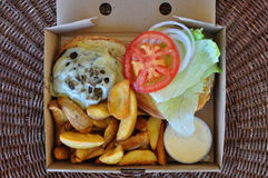 Takeaway burger with fries. Burger with fries and melted cheese mushrooms. Takeaway food in packaging Royalty Free Stock Images