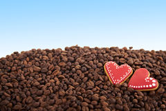 Takeaway ceramic cup and coffee beans on blue background. Close view at gingerbread heart shaped cookies. Scattered coffee beans on blue background. Copy space Royalty Free Stock Photos