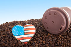 Takeaway ceramic cup and coffee beans on blue background. Close view at at takeway brown ceramic cup gingerbread heart shaped cookies with american flag Stock Photography