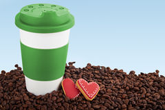Takeaway ceramic cup and coffee beans on blue background. Takeaway green ceramic cup with gingerbread heart shaped cookies. Scattered coffee beans on blue Stock Images