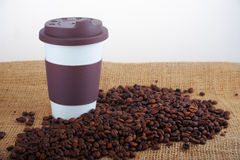 Takeaway ceramic cup and coffee beans on blue background Stock Photography