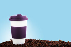 Takeaway ceramic cup and coffee beans on blue background. Takeaway purple ceramic cup and scattered coffee beans on blue background with copy space Stock Photography