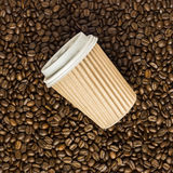 Takeaway coffee cup on beans Stock Image