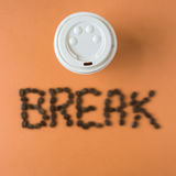 Takeaway coffee cup with word BREAK spelled in beans. Roasted coffee beans spelling out words on an orange background, the word is blurry to denote clarity of Royalty Free Stock Image
