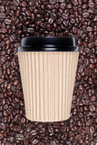 Takeaway disposable coffee cup. Photo of a disposable paper coffee cup with a mixture of arabica and robusta beans in the background Royalty Free Stock Images