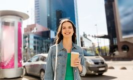 Happy young woman drinking coffee on city street royalty free stock images