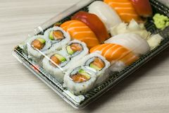Takeaway food plastic containers for Sushi, Sashimi and Futomaki rolls.  Fresh made Sushi set with salmon, prawns, wasabi and ging Royalty Free Stock Images