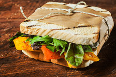 Takeaway grilled toasted sandwich. With pepper,cheese,rocket, spinach and leafy green herbs tied with a brown paper wrapper and string Stock Photo