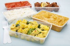 Takeaway Indian Food. A selection of Indian takeaway food in plastic containers on a blue background. Aloo saag (potato spinach curry), chicken tikka masala Stock Photos