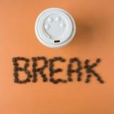Takeaway kaffekopp med ordet AVBROTT som stavas i bönor Royaltyfri Bild
