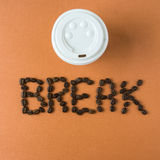 Takeaway kaffekopp med ordet AVBROTT som stavas i bönor Arkivbild