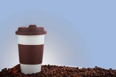 Takeaway keramiska kopp- och kaffebönor på blå bakgrund Arkivbilder
