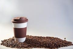 Takeaway keramiska kopp- och kaffebönor på blå bakgrund Fotografering för Bildbyråer