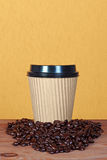 Takeaway paper coffee cup with beans. Photo of a takeway paper disposable cup with coffee beans and copy space to add you own message Royalty Free Stock Photo
