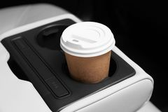 Takeaway paper coffee cup in holder. Inside car stock photo