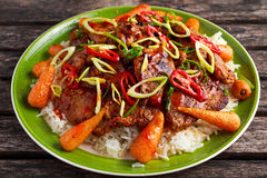 Takeawy classic pork on rice with fried in sticky souce carrots, sprinkle of chillie and spring onion.  Royalty Free Stock Photography