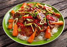 Takeawy classic pork on rice with fried in sticky souce carrots, sprinkle of chillie and spring onion. Stock Images