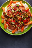 Takeawy classic pork on rice with fried in sticky souce carrots, sprinkle of chillie and spring onion. Stock Photography