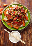 Takeawy classic pork on rice with fried in sticky souce carrots, sprinkle of chillie and spring onion. Royalty Free Stock Photo