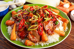 Takeawy classic pork on rice with fried in sticky souce carrots, sprinkle of chillie and spring onion. Takeawy classic pork on rice with fried in sticky souce Royalty Free Stock Photos