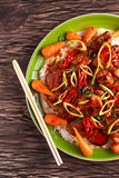 Takeawy classic pork on rice with fried in sticky souce carrots, sprinkle of chillie and spring onion. Stock Image