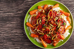 Takeawy classic pork on rice with fried in sticky souce carrots, sprinkle of chillie and spring onion. Royalty Free Stock Photos