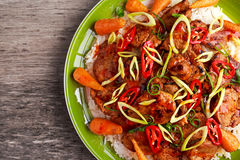 Takeawy classic pork on rice with fried in sticky souce carrots, sprinkle of chillie and spring onion. Royalty Free Stock Image