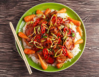 Takeawy classic pork on rice with fried in sticky souce carrots, sprinkle of chillie and spring onion. Stock Photo