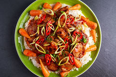 Takeawy classic pork on rice with fried in sticky souce carrots, sprinkle of chillie and spring onion. Takeawy classic pork on rice with fried in sticky souce Stock Photo