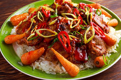 Takeawy classic pork on rice with fried in sticky souce carrots, sprinkle of chillie and spring onion. Takeawy classic pork on rice with fried in sticky souce Royalty Free Stock Image