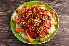 Takeawy classic pork on rice with fried in sticky souce carrots, sprinkle of chillie and spring onion. Stock Photos
