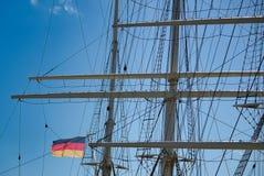 Takelung und Maste eines großen Segelschiffs vor einem blauen Himmel mit der schwarz-rot-goldenen Flagge des Zustandes Deutschlan stockfoto