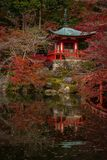 Small red Japanese shrine with its reflection in the pond royalty free stock photography