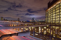 Taken on Brooklyn Bridge at Twilight with a well lit building on Brooklyn on the right and heavy traffic below Stock Photos