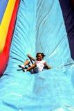 Little girl enjoys sliding down an inflatable slide. stock photos