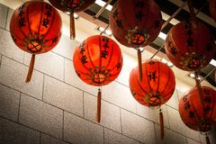 Hanging Chinese Red lanterns against a granite wall royalty free stock images