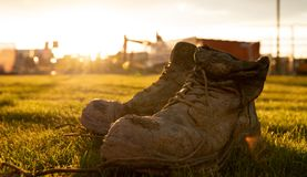 Safety Boots at a construction site covered in mud in front of a bright sunset royalty free stock images