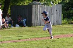 Little League player runs to second base