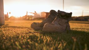 4K Muddy safety boots left in a field near a construction site with a sunrise behind