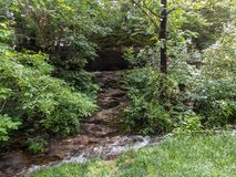 Small Cave and Stream. Taken near Springfield Missouri, Doling Park. Early Spring. Image shows a small cave, with a small fresh water stream, among the greens of stock photo