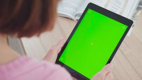 Taken over the shoulder: young woman uses a tablet with a green screen. Taken over the shoulder: a young woman uses a tablet with a green screen. She scrolls the stock video