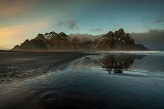 The Vestrahorn mountain range taken from Stocksness beach during sunset. Taken from the quiet Stocksness beach. Complete with a reflection of the mountains in stock photography