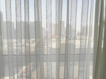 Thin white curtain see through with city view behind. Taken from a room on high floor of buildings in China stock photo