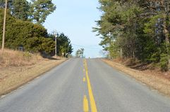 Short rural road with lines. Taken in rural Virginia. You can barely see a warning for a curve and a stop sign ahead Royalty Free Stock Photos