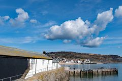 Clouds gather across Lyme Regis. Taken on a sunny March day, from the furthest reaches of the Cobb, this captures a blue but cloudy sky over the town of Lyme royalty free stock photo